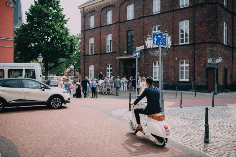 Der Bräutigam fährt auf seiner Vespa zum historischen Standesamt in Rheinberg. Die Gesellschaft wartet schon davor.