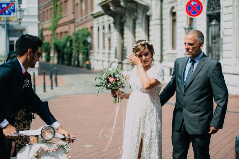 Der Bräutigam steigt von seiner Vespa ab während die Braut sich eine Träne weg wischt.